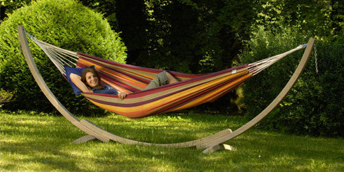 Woman lying in hammock on a wooden stand