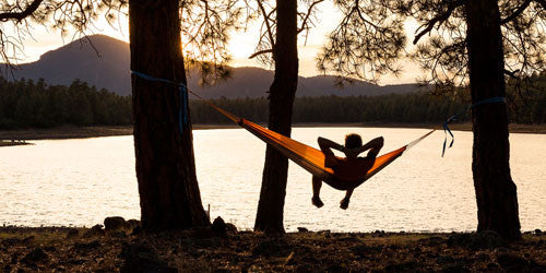 Man sitting in travel hammock overlooking lake