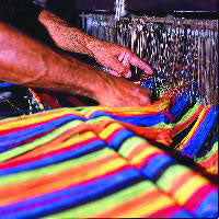 Hands knotting threads at weaving loom for hammocks