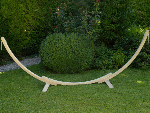 Arched wooden Apollo stand in garden.