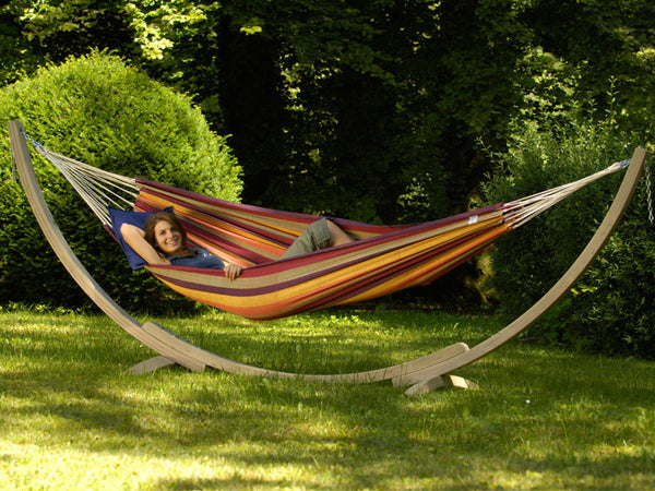Girl lying in striped hammock suspended on Apollo hammock stand