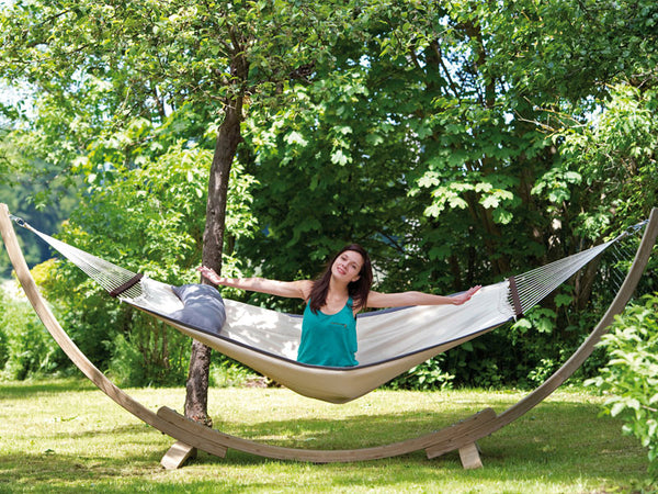 Girl sitting on hammock suspended on Apollo hammock stand.
