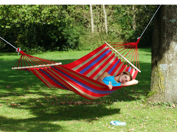 Woman lying flat in Aruba red blue yellow striped hammock.