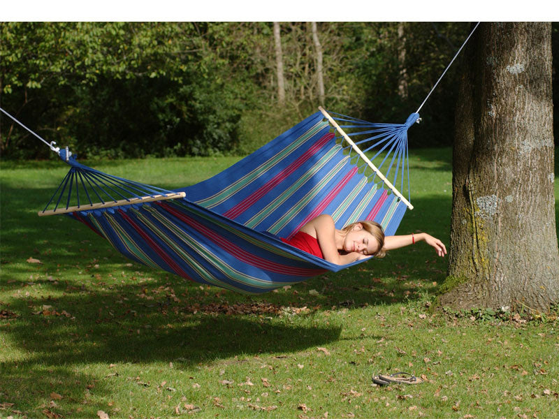 Woman lying flat in Aruba blue striped hammock.