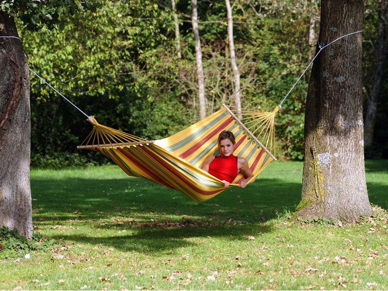 Woman lying flat in Aruba yellow red green striped hammock.