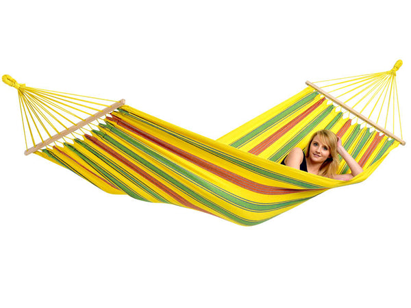 Woman lying flat in Aruba red blue yellow striped hammock with white background