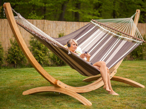 Woman sitting sideways in large hammock suspended from Arcus stand