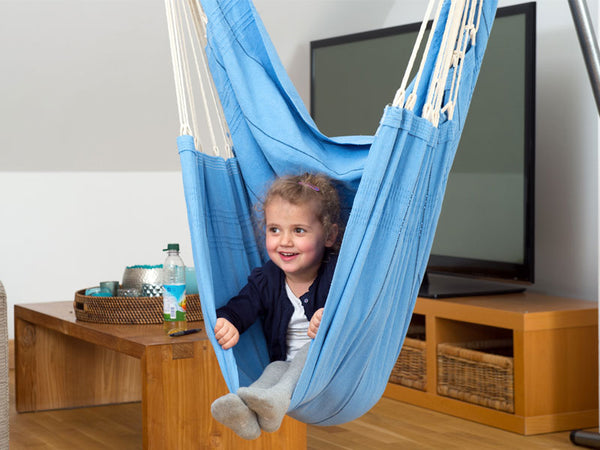 Child sitting in Artista Blue Hammock Chair indoors