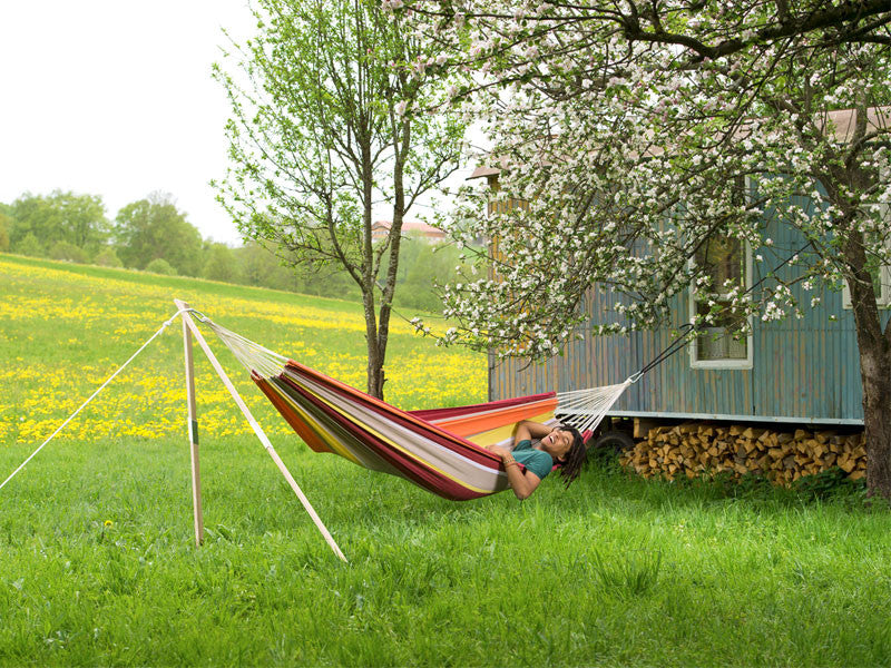 Man lying in colourful striped Acerola Barbados hammock supported by Madera tripod stand
