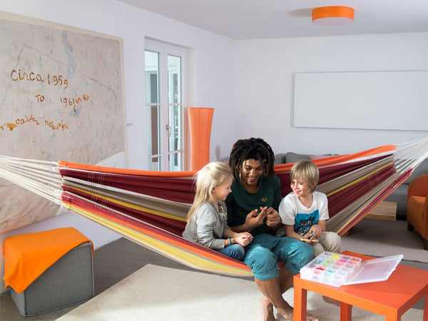 Family sat in colourful striped Acerola Barbados hammock hung in house