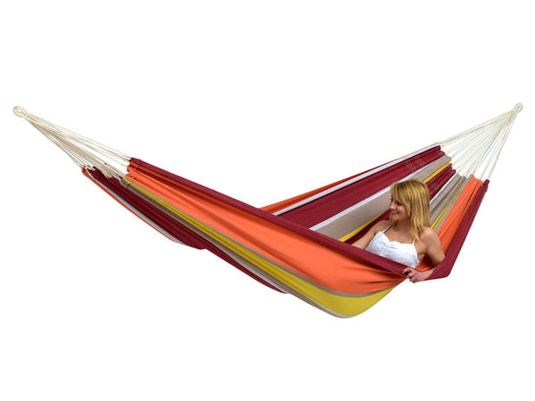 Woman lying in colourful striped Acerola Barbados hammock