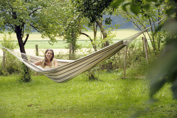 Woman sitting up in cappuccino with thin brown stripes Barbados hammock