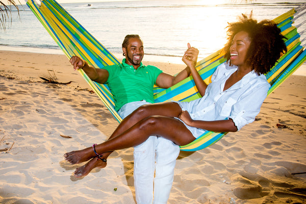 Couple relaxing on beach in green blue yellow striped Lemon Barbados hammock