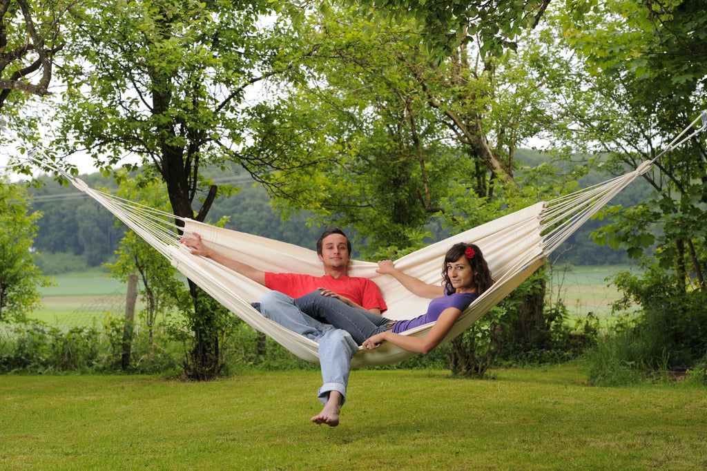 Couple relaxing in white Natura Barbados hammock