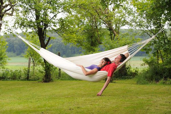 Couple lying in white Natura Barbados hammock