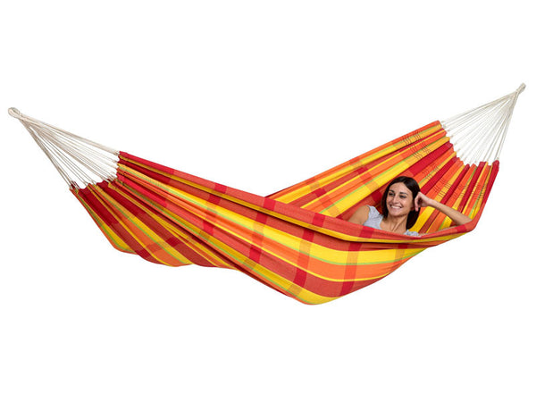 Woman lying in oranges and yellow striped Papaya Barbados hammock