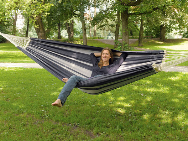 Woman lying sideways in silver Paradiso hammock in garden.