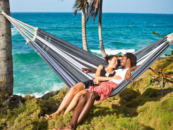 Couple lying sideways in silver Paradiso hammock by sea.