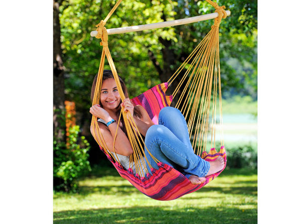Close up of girl with knees drawn up in garden sat in Belize Vulcano Hammock Chair.
