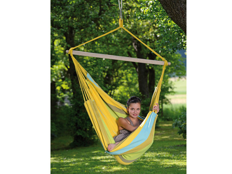 Girl curled up in yellow striped Limona Bogata hammock chair suspended in garden.