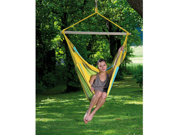 Girl sat in yellow striped Limona Bogata hammock chair suspended in garden
