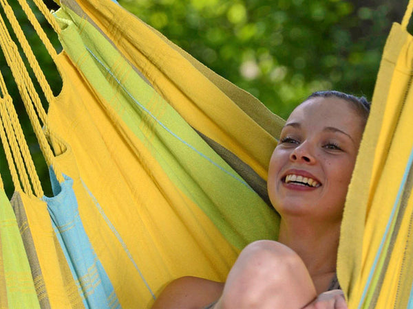 Close up of girl sat in yellow striped Limona Bogata hammock chair.