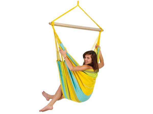 Girl sat in yellow striped Limona Bogata hammock chair with white background.
