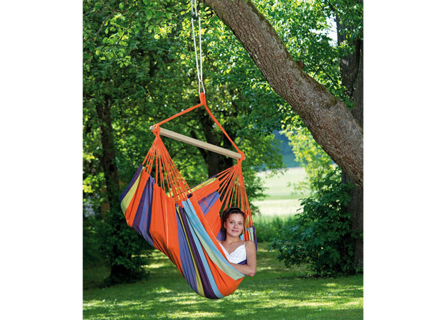 Girl sat sideways in orange striped Mandarina Bogata hammock chair suspended in garden.