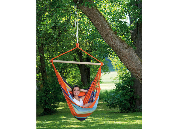 Girl curled up in Mandarina striped Mandarina Bogata hammock chair suspended in garden.