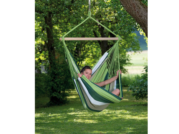 Girl sat sideways in green striped Oliva Bogata hammock chair suspended in garden.