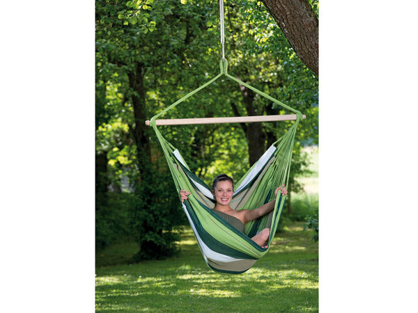 Girl sat in green striped Oliva Bogata hammock chair suspended in garden.