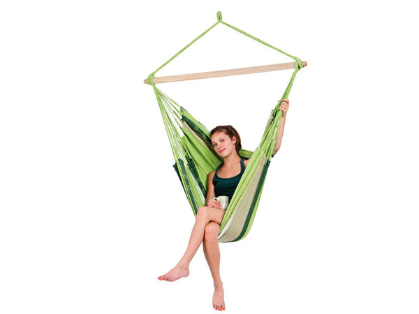 Girl sat in green striped Oliva Bogata hammock chair with white background.