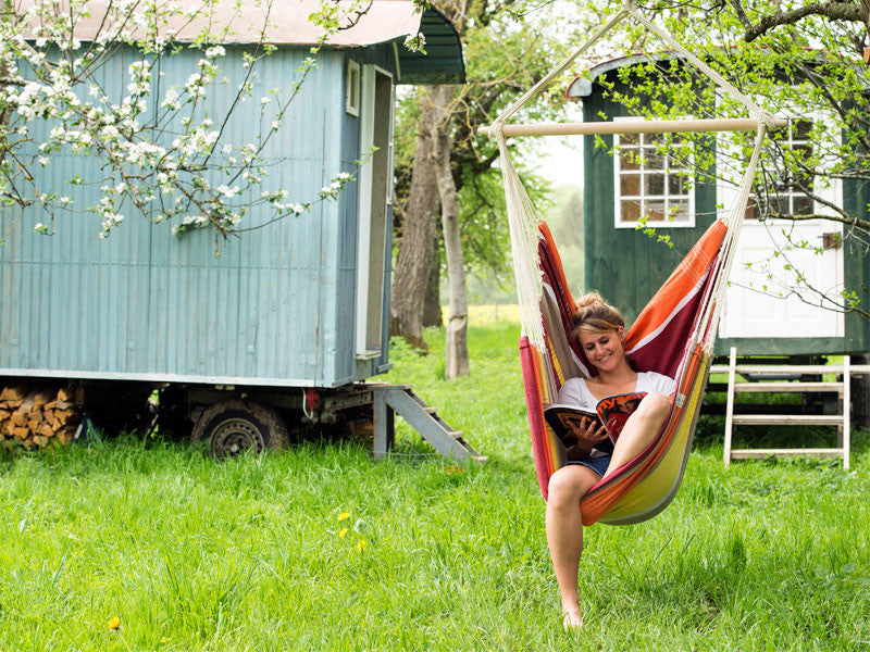 Woman reading in Brasil Acerola Hammock Chair with shepherds hut behind.
