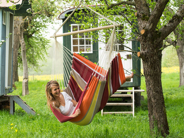 Woman sat sideways in Brasil Acerola Hammock Chair with shepherds hut behind.