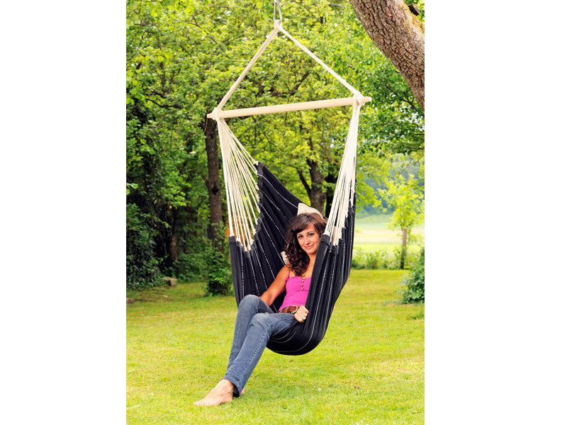 Woman sat in Black Brasil Hammock Chair in garden.