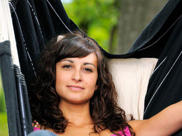 Close up of woman sat in Black Brasil Hammock Chair.