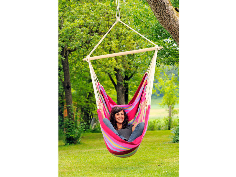 Girl sat in Grenadine Brasil Hammock Chair in garden.
