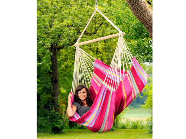 Girl sat sideways in Grenadine Brasil Hammock Chair in garden.
