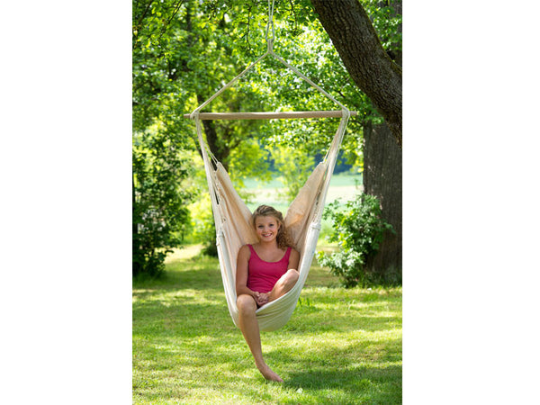 Girl sat in Natura Brasil Hammock Chair in garden.