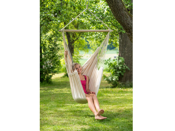 Girl swinging in Natura Brasil Hammock Chair in garden.