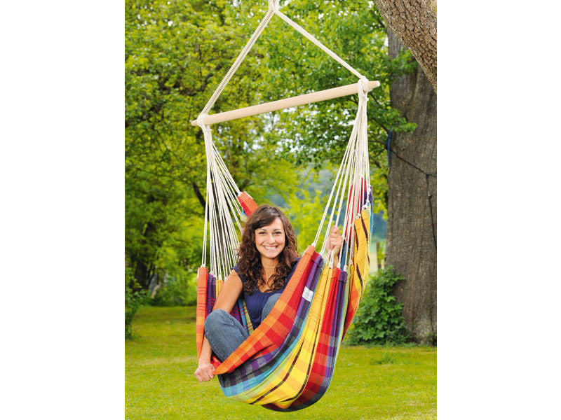 Girl sat in Rainbow Brasil Hammock Chair in garden.