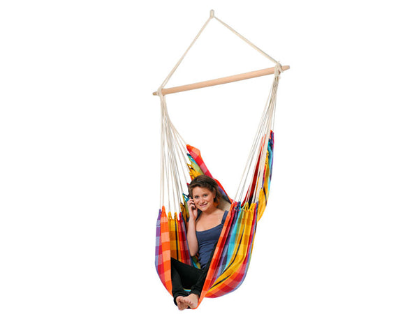 Woman sat in Brasil Rainbow Hammock Chair with white background.