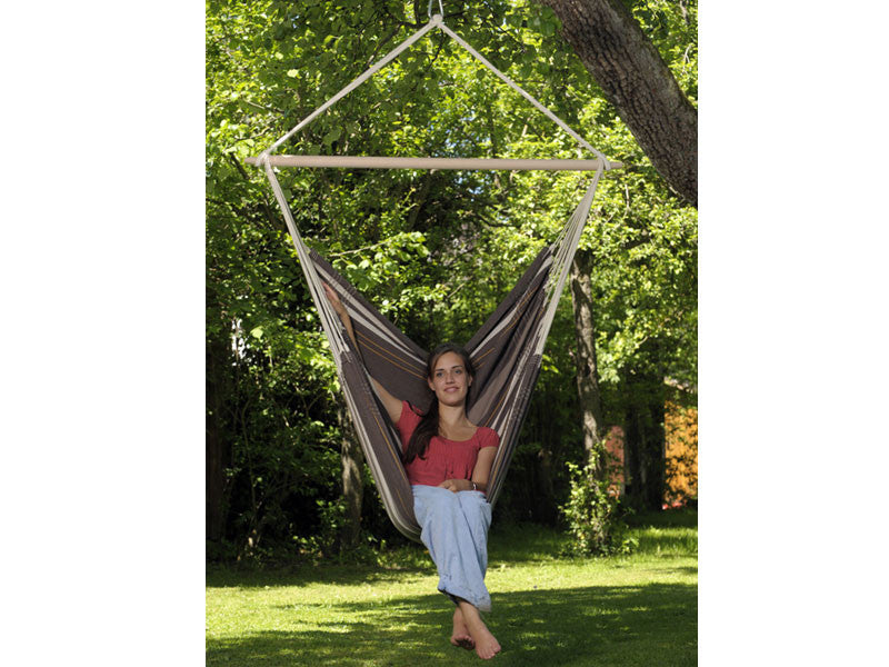 Woman sat in Cafe Brasil Gigante Hammock Chair in garden.