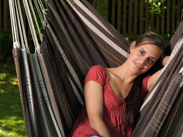 Close up of woman sat in Cafe Brasil Gigante Hammock Chair in garden.