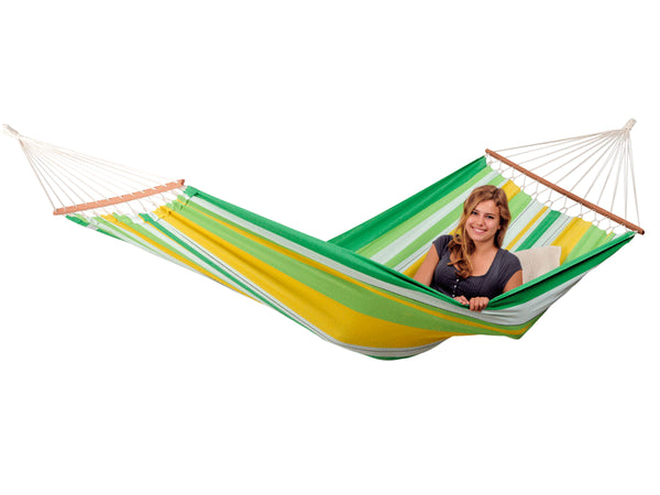 Woman lying in striped green yellow white Brasilia hammock with spreader bar