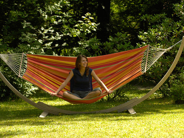 Woman sat in striped colourful hammock with wooden stand