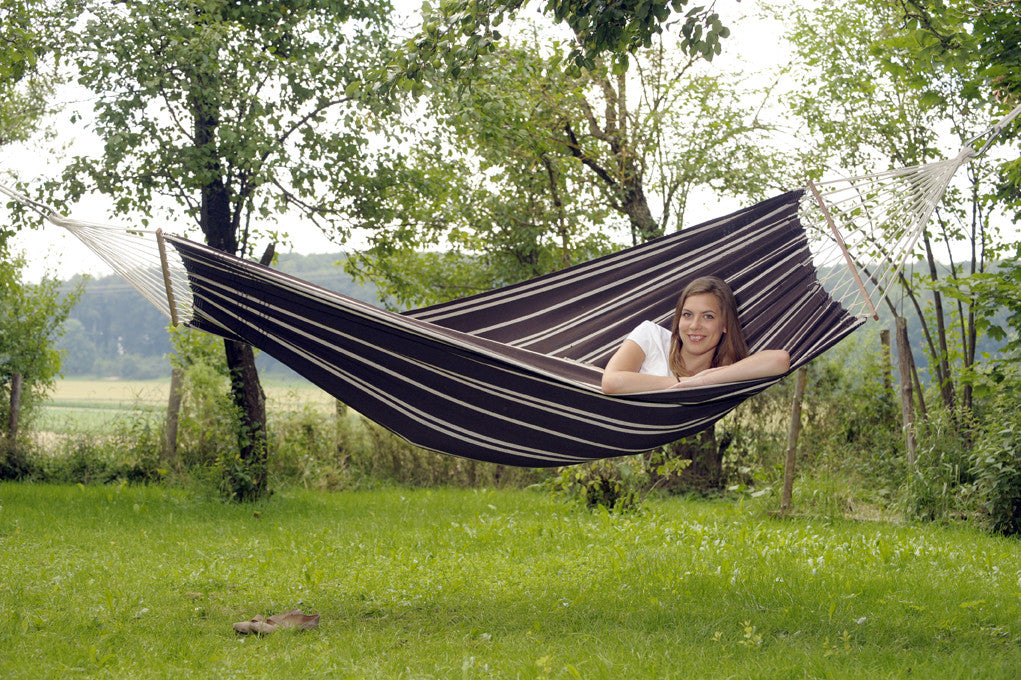 Woman resting in mocca with stripes Brasilia hammock with spreader bar