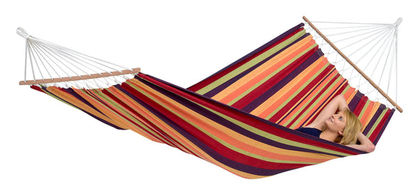 Woman relaxing in tropical striped Brasilia hammock with spreader bar
