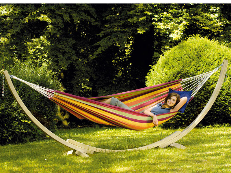 Woman lying in Lambada striped colourful Tropical hammock with wooden stand