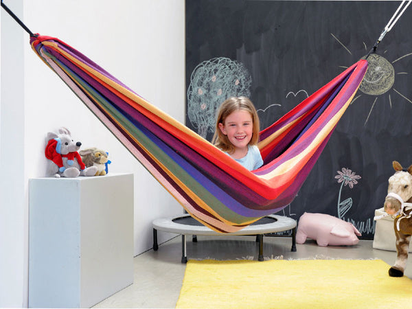 Young girl sat in Chico Rainbow Hammock in bedroom.